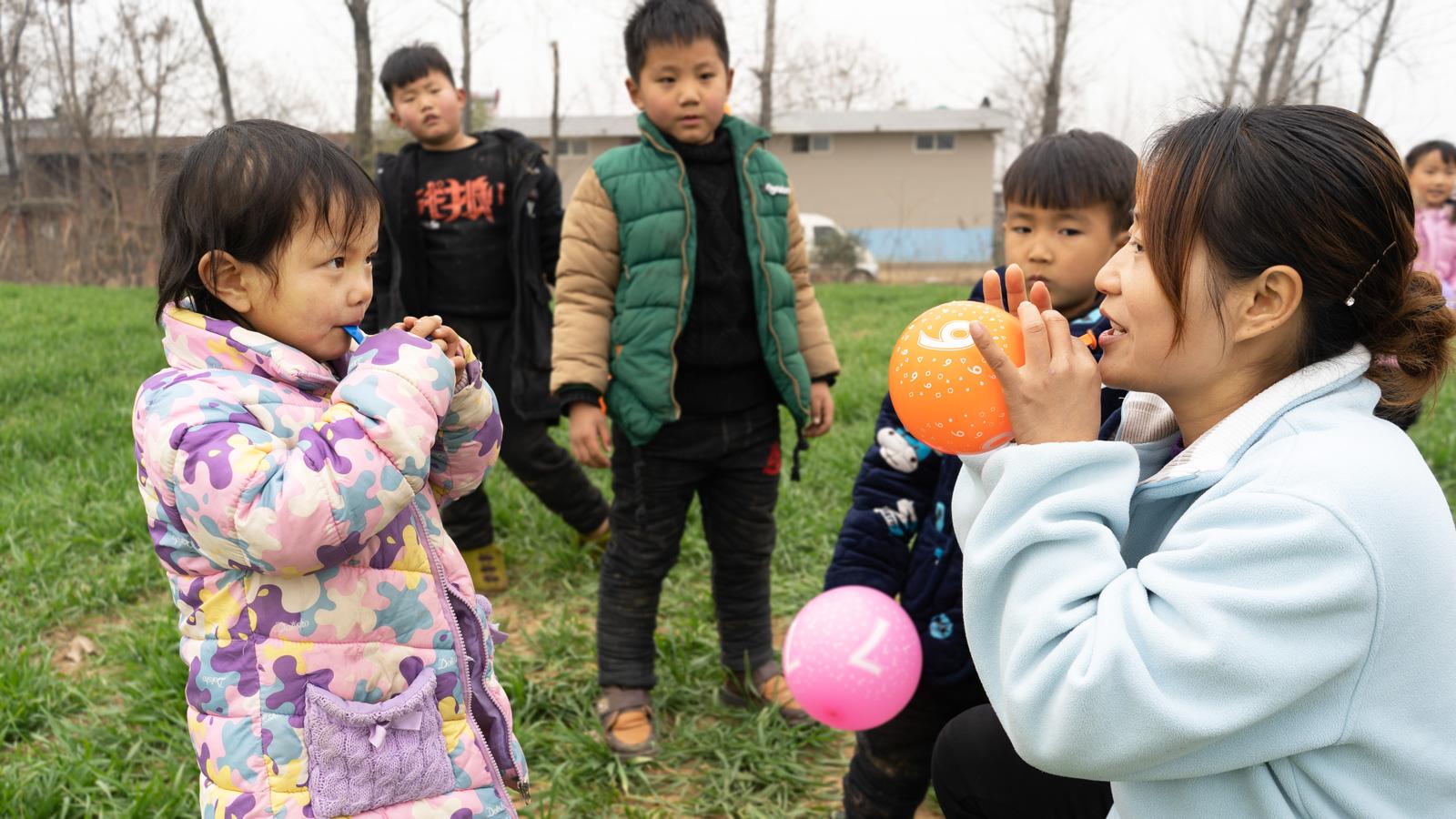 Zhenzhen blows a balloon with her teacher
